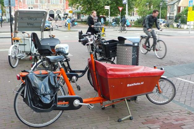 A baksfiets -- a cargo bike. It is not unusual to see a parent with one or two children enjoying a ride in the front.